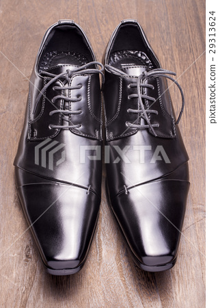 Front-facing black leather shoes on a wooden table 29313624