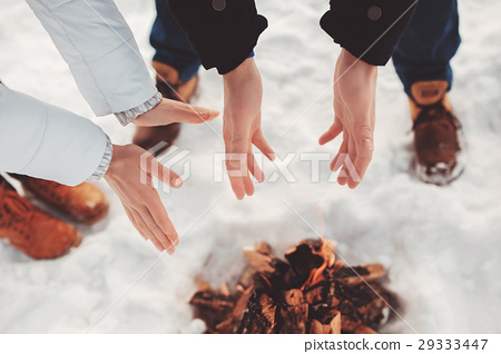 Man and woman warm their hands near fire 29333447