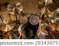 male musician playing drums and cymbals at concert 29343075
