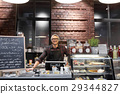 happy seller man or barman at cafe counter 29344827