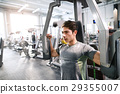 Hispanic man in gym sitting on bench, working out 29355007