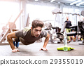 Young fit hispanic man in gym doing push ups 29355019
