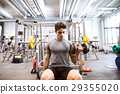 Hispanic man in gym sitting on bench, working out 29355020