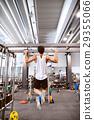 Hispanic man in gym doing pull-ups on horizontal 29355066