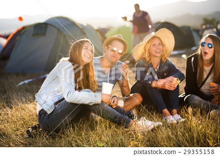 Teenagers sitting on the ground in front of tents 29355158