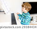 Beautiful little kid boy playing piano in living 29384434