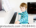 Beautiful little kid boy playing piano in living 29384441