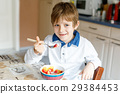 little blond school kid boy eating cereals with 29384453