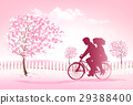 Couple riding a bike in a park. 29388400