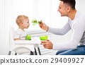 father feeds baby from spoon 29409927