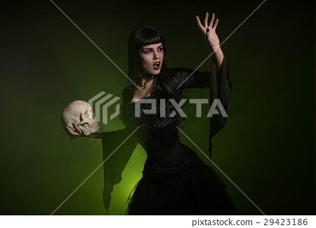 Sensual witch holding a skull in her hand 29423186