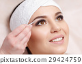 Young woman tweezing her eyebrows in beauty saloon 29424759