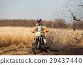 Enduro bike rider in a field in autumn 29437440