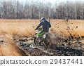 Enduro bike rider in a field with dry grass in autumn 29437441