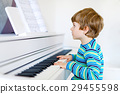 Beautiful little kid boy playing piano in living 29455598
