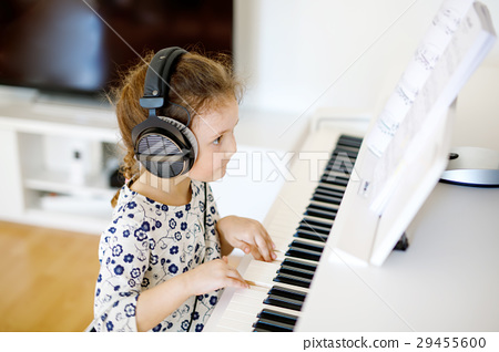 Beautiful little kid girl playing piano in living 29455600