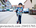 Little kid boy in helmet riding with his scooter 29455765