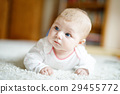 Adorable newborn baby girl lying on belly in white 29455772