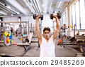 Hispanic man in gym sitting on bench, working out 29485269
