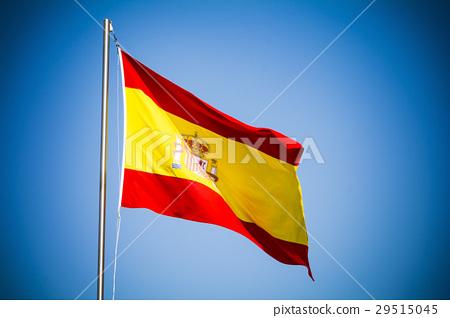 Spain flag fluttering against blue sky on sunny da 29515045