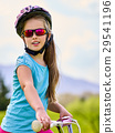 Child traveling bicycle in rainbow goggles and 29541196