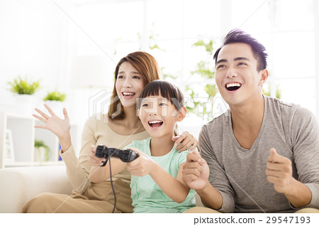 Laughing family playing video games in living room 29547193