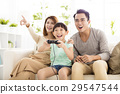 Laughing family playing video games in living room 29547544