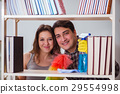 Wife and husband cleaning dust from bookshelf 29554998