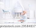 Baby boy drinking milk in sunny nursery 29584837