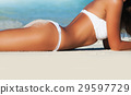 Woman lying on sea beach in bikini 29597729