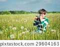 Child wathing in camera on the field with 29604163
