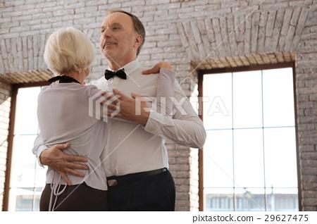 Optimistic aging dance couple enjoying waltz in 29627475