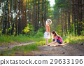 Two adorable little sisters hiking in a forest on summer 29633196