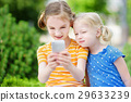 Two cute little sisters playing outdoor mobile game on their smart phones 29633239