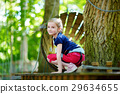Adorable little girl enjoying her time in climbing adventure park 29634655