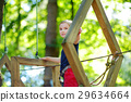 Adorable little girl enjoying her time in climbing adventure park 29634664