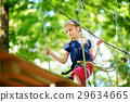 Adorable little girl enjoying her time in climbing adventure park 29634665