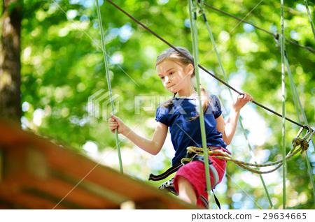 Adorable little girl enjoying her time in climbing adventure park 29634665