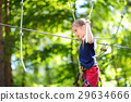 Adorable little girl enjoying her time in climbing adventure park 29634666