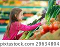 Little girl choosing a leek in a food store or supermarket 29634804