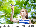Adorable little girl playing with small toy airplane outdoors 29634806