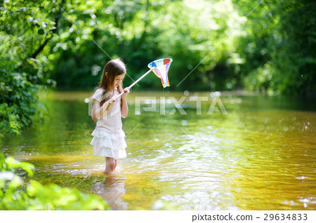 Cute little girl playing in a river catching rubber ducks with her scoop-net 29634833