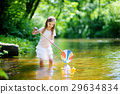 Cute little girl playing in a river catching rubber ducks with her scoop-net 29634834