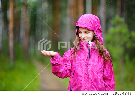 Adorable little girl playing happily in the rain 29634843