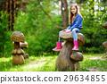 Cte little girl having fun on giant wooden mushrooms 29634855