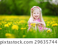 Adorable little girl in blooming dandelion meadow on spring day 29635744