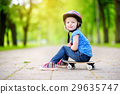 Cute little preteen girl wearing helmet sitting on a skateboard 29635747