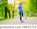 Pretty little girl learning to skateboard outdoors 29635752