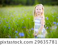 Cute little girl having fun a blooming cornflower field 29635781