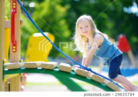 Cute little girl having fun on a playground 29635784